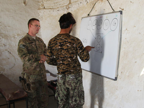 Sgt. Randall Schamber teaches Afghan soldiers and contractors how to properly wire the output of an electrical generator at Forward Operating Base Nolay.