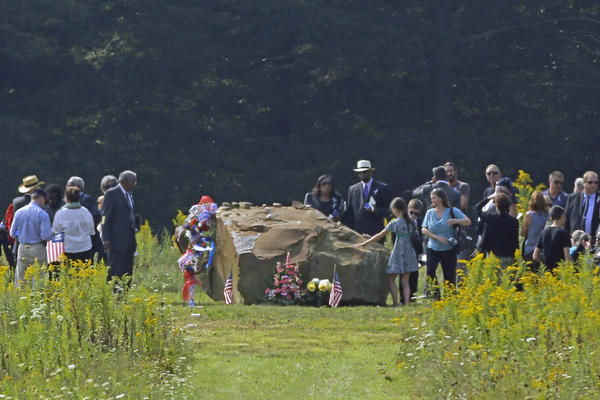 The family and friends of the passengers and crew of Flight 93 gather around a bolder that marks the plane's impact area, during a memorial service at the Flight 93 National Memorial in Shanksville, Pa.