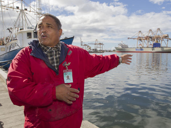 John Hernandez of Kailua, Hawaii, who owns John's Fresh Fish, is shown on Thursday. In the background at right is a container ship owned by Matson Navigation Co. A pipe maintained by the company cracked and caused the molasses spill.
