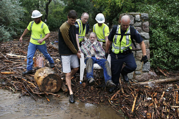 Will Pitner is rescued by emergency workers and neighbor Jeff Writer on Friday, after a night sheltering on high ground above his home as it filled with water from a surge at the base of Boulder Canyon, Colo.