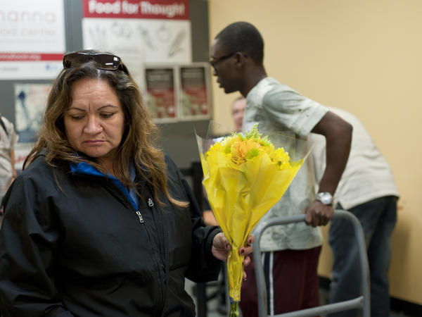 Judith Prado picks a bouquet of flowers to take with her other donations from the food pantry.
