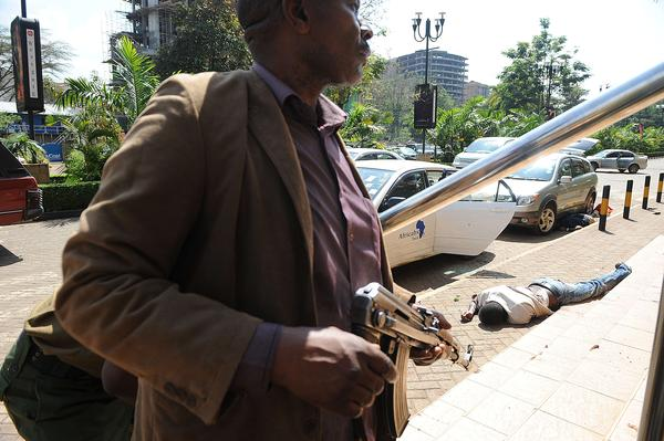 The body of a man lies on the ground as plainclothes policemen try to gain entry into the Westgate mall on Saturday. Ten to 15 attackers remain in the mall and Kenyan forces control the security cameras inside the shopping center, Lenku said.