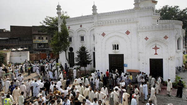 People gather outside All Saints Church in Peshawar, Pakistan, Sunday, after a suicide bombing attack killed scores of people earlier in the day, officials said.
