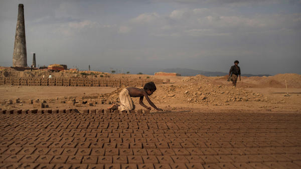 Near Islamabad, Pakistan, 6-year-old Jabro Mounir was arranging bricks this summer — part of his daily work at a brick-making facility. He earns a little less than $2 per day.