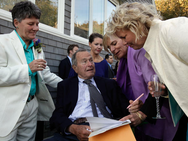 Former President George H.W. Bush prepares to sign the marriage license of friends Helen Thorgalsen, right, and Bonnie Clement, left, in Kennebunkport, Maine, as officiant Nancy Sosa, third right, and Helen's daughter Lindsey look on. Bush was an official witness at the Sept. 21, 2013, wedding.