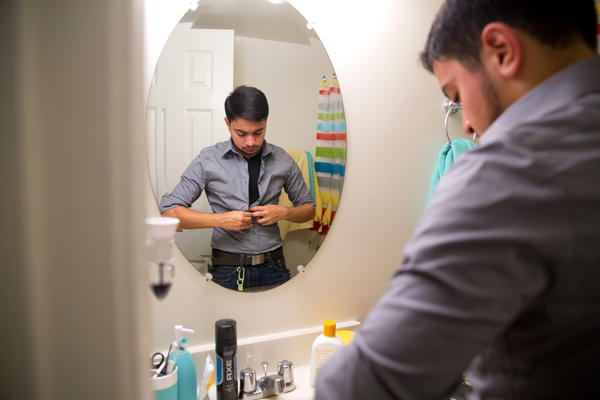 """Younes dresses for work in the morning. He says that while telling his story will be his way of putting himself out there, that doesn't make it """"open season"""" for strangers to bluntly ask about personal things like his sexuality. """"Everyone's got a different story. There's no cut and dry mold for being transgender,"""" he said."""