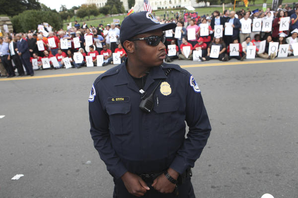 Capitol Police officer G. Stith keeps the crowd off the street during the rally.