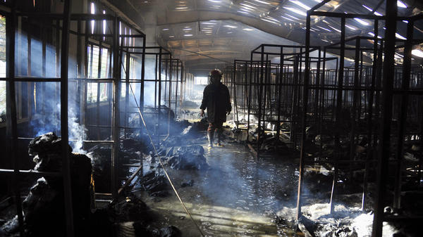 A Bangladeshi firefighter stands inside a damaged garment factory after it caught fire in Gazipur outside the capital, Dhaka, on Wednesday. The fire killed at least 10 people at the factory.