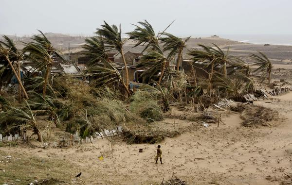 "A woman returns to the cyclone-hit Arjipalli village on the Bay of Bengal coast in Orissa state, India, on Sunday. The state's Chief Minister Naveen Patnaik says that a full recovery will be a ""big challenge."""