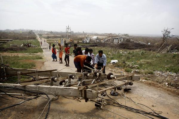 People try to remove an electric pole that fell down in Arjipalli village. Mass evacuations spared India the widespread deaths many had feared from a powerful cyclone that roared ashore over the weekend.