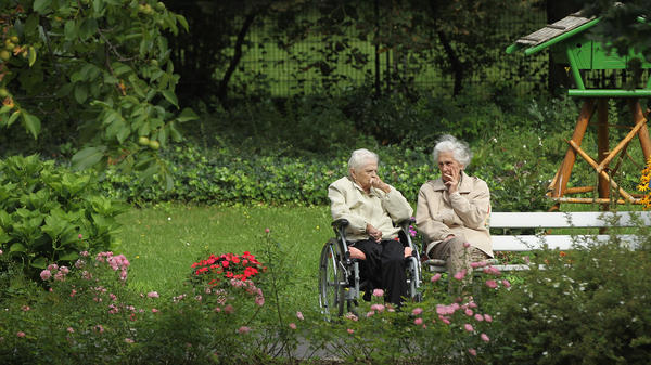 "Two German women chat in the gardens of a senior care home in Berlin. Germany is grappling with a rapidly aging population: By 2050, almost a third of Germans will be 65 years or older, and a growing ""Grandma export"" trend has set hands wringing."