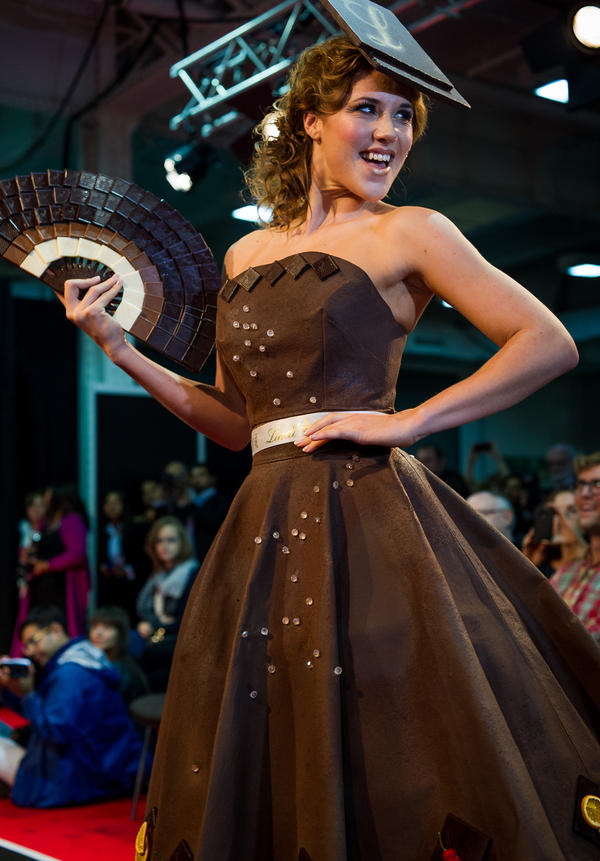 """""""Eternal Diamond,"""" an A-line dress hand-painted with 40 pounds of Lindt chocolate. It's adorned simply along the hem with chili and orange segments, flavors used in speciality Lindt chocolate bars. The fan and hat are also crafted from chocolate, of course."""