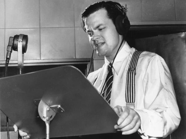 Orson Welles delivering a radio broadcast in 1938, the same year he aired his <em>War of the Worlds</em> fake news program.