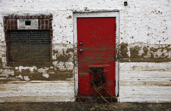 Sand marks the floodwater line on the side of a house in Long Beach, N.Y.