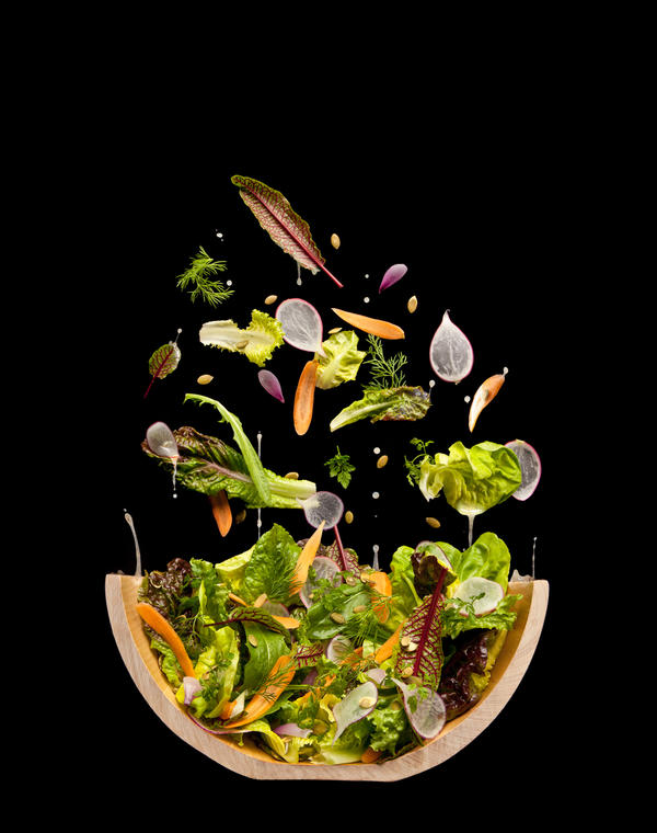A tossed salad that isn't tossed. The photographers hung a piece of black velvet at a 70 degree angle and then pinned the leaves and nuts in place.