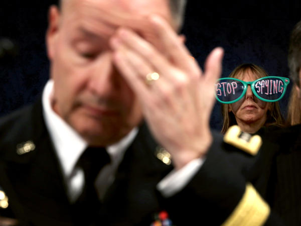 A protester appears behind Gen. Keith Alexander, director of the National Security Agency, at a hearing of the House intelligence committee this week in Washington.