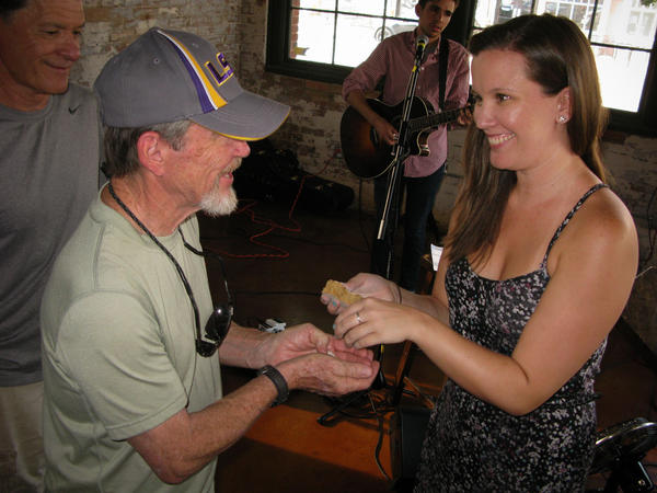Leah Stanfield, a leasing agent in Fort Worth and regular attendee of Church-in-a Pub, hands out bread during communion at the tavern.