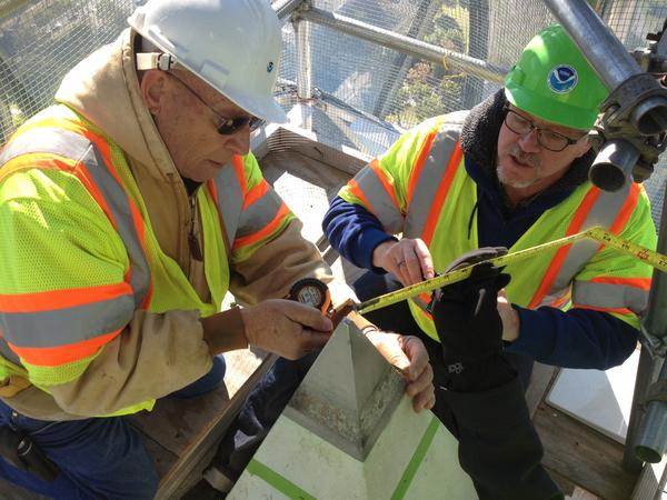 Don Breidenbach, left, and Kendall Fancher take measurements of at the very top of the Washington Monument.