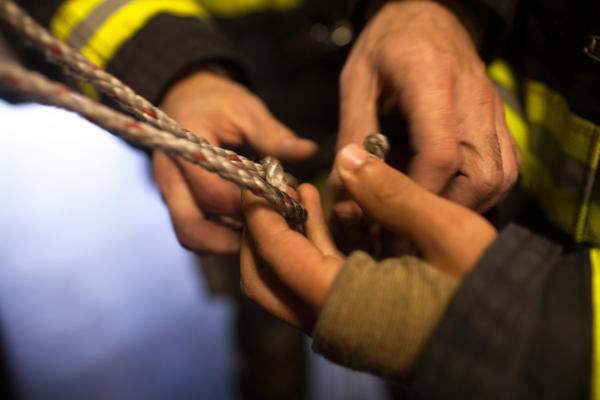 Firefighter William Shelton trains probationary firefighter and veteran Victor Ramos on ropes and knots at the 16th Street Firehouse.