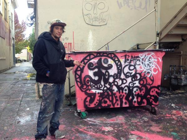 "22-year-old ""James"" from Tillamook, Oregon shows off his graffiti art in an Olympia alleyway. (Austin Jenkins/Northwest News Network)"