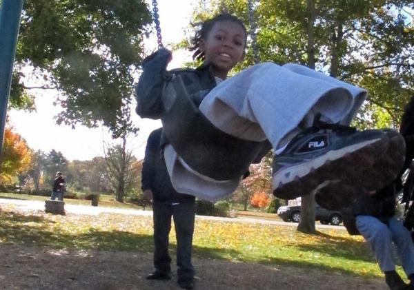Melody Salhudin hits the swings during a break from her walk. (Martha Bebinger/WBUR)