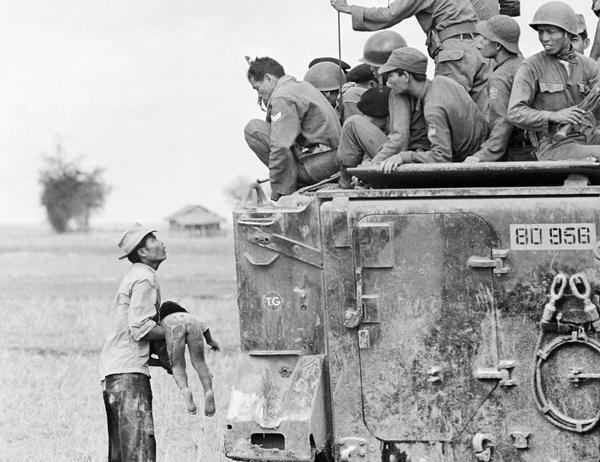 A distraught father holds the body of his child as South Vietnamese Rangers look down from their armored vehicle, March 19, 1964. The child was killed as government forces pursued guerrillas into a village near the Cambodian border. From the portfolio by photographer Horst Faas that received the 1965 Pulitzer Prize for Photography. (Horst Faas/AP)