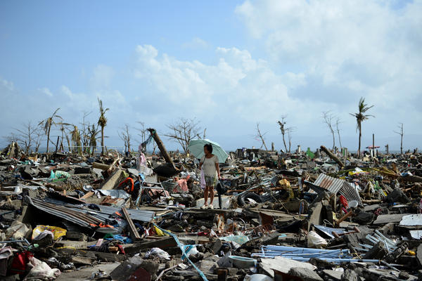 A survivor walks among the debris of houses destroyed by Typhoon Haiyan in Tacloban, Philippines. Across the Philippines an estimated 9.5 million people were affected, at least 620,000 were forced from their homes and it's feared that more than 10,000 were killed.
