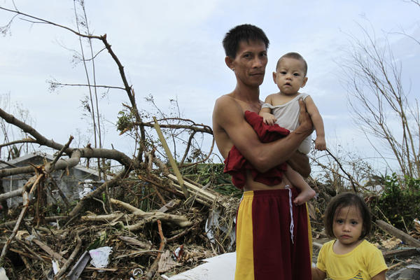 Roy Cagbian, 28, stands with his daughters, 7-month-old Shandev and 3-year-old Ashley in front of their destroy home in Tacloban.