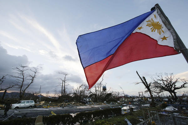 A Philippine flag stands in the devastation in Tacloban. A weakened Haiyan hit Vietnam on Monday.