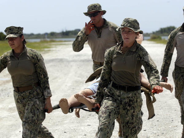 Two female Marines carry a mock wounded person as they participate in a drill at Camp Lejeune, N.C. They were among the first female participants to receive this training after the military lifted its ban on women serving in combat roles.