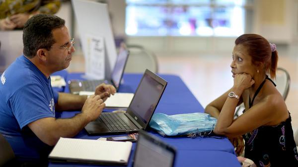 Mario Ricart , an insurance agent with Sunshine Life and Health Advisors, talks with Naylie Villa about buying insurance under the Affordable Care Act on Nov. 5 in Miami.