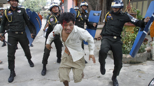 An injured Cambodian worker escapes from riot police in the compound of a Buddhist pagoda in Phnom Penh, Cambodia, on Tuesday. Police fired live ammunition at protesting garment workers outside the capital, injuring at least 20 people and killing a bystander.