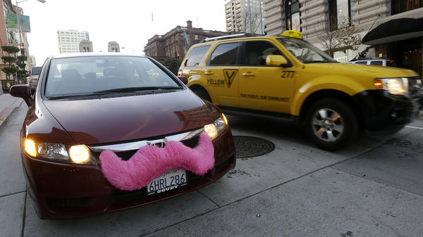 A Lyft driver in San Francisco drops off a passenger as a taxi passes by. The smartphone app lets city dwellers hitch rides from strangers.