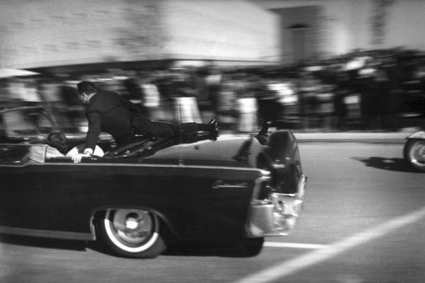 The limousine carrying President Kennedy races toward Parkland Hospital seconds after he was shot. Secret Service agent Clinton Hill rides on the back of the car; Mrs. Connally, bends over her wounded husband; and Mrs. Kennedy leans over the president.
