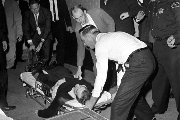 Oswald is placed on a stretcher after being shot in the stomach in Dallas on Nov. 24. Nightclub owner Jack Ruby shot and killed Oswald as the prisoner was being transferred through the underground garage of Dallas police headquarters.