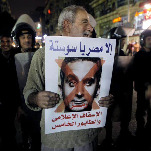 "A supporter of Sissi holds a poster with a photo of Bassem Youssef, the man known as ""Egypt's Jon Stewart,"" during a protest in Cairo. The sign reads, ""not Egypt, you are degrading to the media, fifth column."""