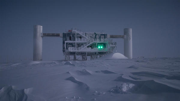 The average temperature in winter is about -72 degrees Faharenheit. The IceCube Lab is illuminated in the moonlight.