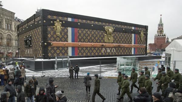 Tourists and visitors pass by a two-story Louis Vuitton suitcase erected at the Red Square in Moscow on Wednesday. Politicians didn't like it, the public didn't like it, so the gigantic Louis Vuitton suitcase is being booted out of Red Square.