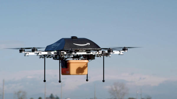 In an image taken of a test flight, an Amazon Prime Air drone carries a package. The online retailer could begin 30-minute deliveries within four to five years, CEO Jeff Bezos told <em><em>60 Minutes</em></em> Sunday.