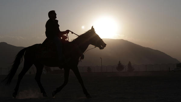 An Afghan man rides a horse at sunset on Nadir Khan hill in Kabul, Afghanistan. Auliya Atrafi paid thousands of dollars and risked his life to escape the Taliban-controlled country, only to return after 12 years living in England.