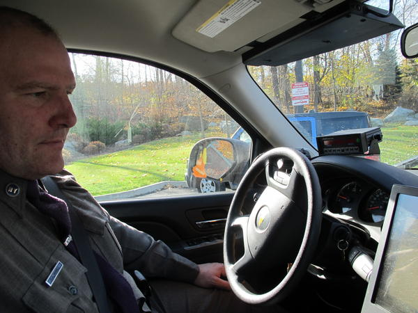"New York State Trooper Clayton Howell checks a screen that displays driving records inside his patrol SUV. The vehicle allows him to see whether passing drivers are on their phones. ""It's a bird's-eye view,"" he says."
