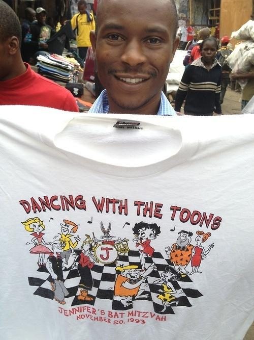 Paul Warambo holds up a used T-shirt for sale in Nairobi, Kenya. With the help of the internet, we found the original owner