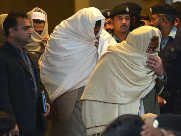 """Pakistani policemen escort newly identified missing persons — people who """"disappeared"""" after being taken away by the country's powerful security agencies — as they leave the Supreme Court building in Islamabad on Dec. 7."""