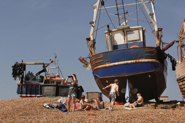 A family relaxes near fishing boats on the Hastings seafront in 2009.