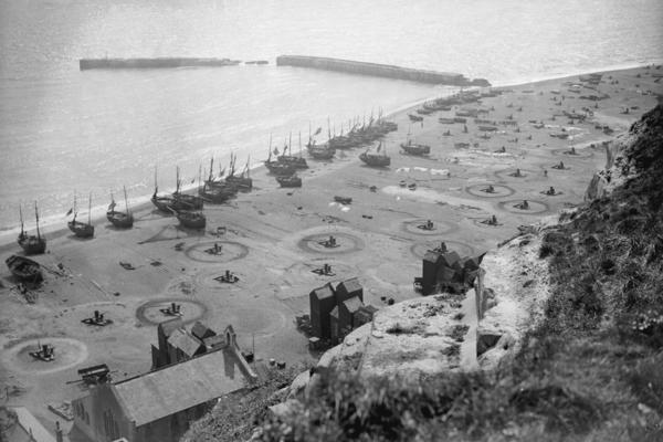 Hastings, on England's south coast, is an ancient town that overlooks the English Channel. The fishing fleet there launches from the beach, not a harbor. This image from 1933 shows a fleet of small boats hauled up onto the beach.