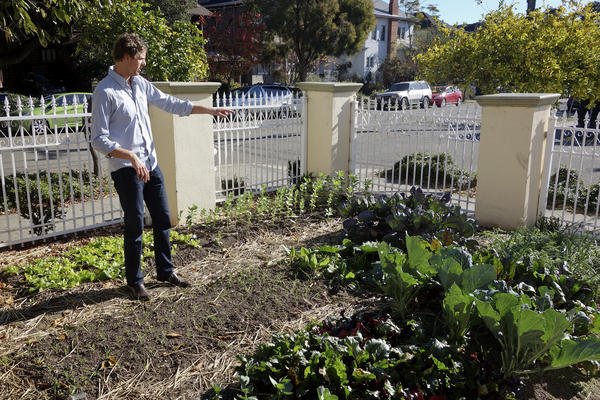 Ben Provan, co-founder of a co-living home in Berkeley, tends to a sprawling vegetable garden that grows enough food to feed the residents.