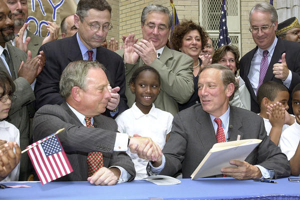 Bloomberg shakes hands with Gov. George Pataki after Pataki signed city school governance legislation June 12, 2002. The legislation gave Bloomberg control of the city's school system.
