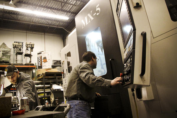 Workers at Machine Inc. edit program code on a new $500,000 machine that will not just do the work of many people, but of several older machines. It will cut metal on five axes simultaneously, and to exact specifications within 50 millionths of an inch.