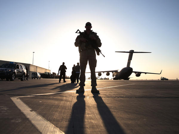 A member of the U.S. armed forces stands guard near a C-17 military aircraft in the southern city of Kandahar on Dec. 8. The U.S. still has about 50,000 military personnel in Afghanistan, but most will be withdrawn next year.