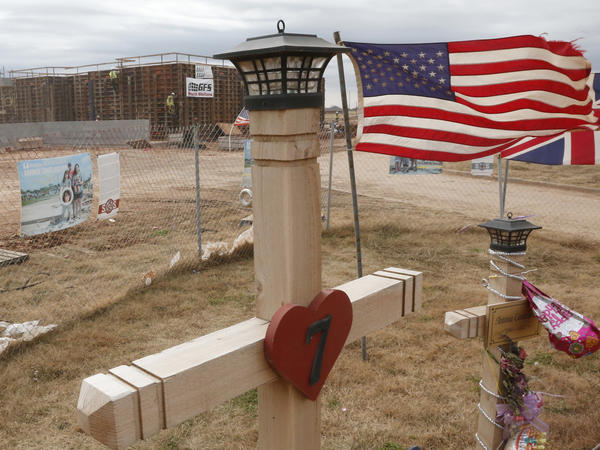 Crews work on a safe room for the new Plaza Towers Elementary school in Moore, Okla., behind crosses erected for the seven students who died in the May tornado.